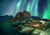 Northern lights over fishing village with mountain range on coastline at Hamnoy, Lofoten