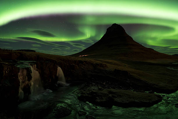 Northern lights over  Kirkjufell mountain, Grundarfjordur, Snaef Aerial view of  double cascade waterfall, Kirkjufellsfoss, and pointed mountain of Kirkjufell, at Grundarfjordur in winter, with  green curving bands of Northern Lights and lenticular clouds in a starry sky, Snaefellnes, Iceland lenticular cloud stock pictures, royalty-free photos & images