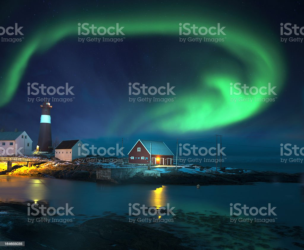 Northern lights (Aurora borealis) over lighthouse seaside in winter royalty-free stock photo