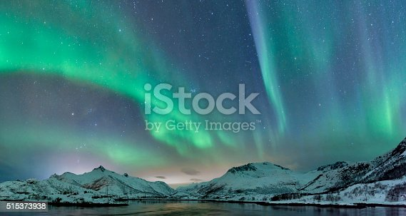 Northern Lights, polar light or Aurora Borealis in the night sky over the Lofoten islands in Northern Norway. Wide panoramic image with snow covered mountains and a lake in the foreground.