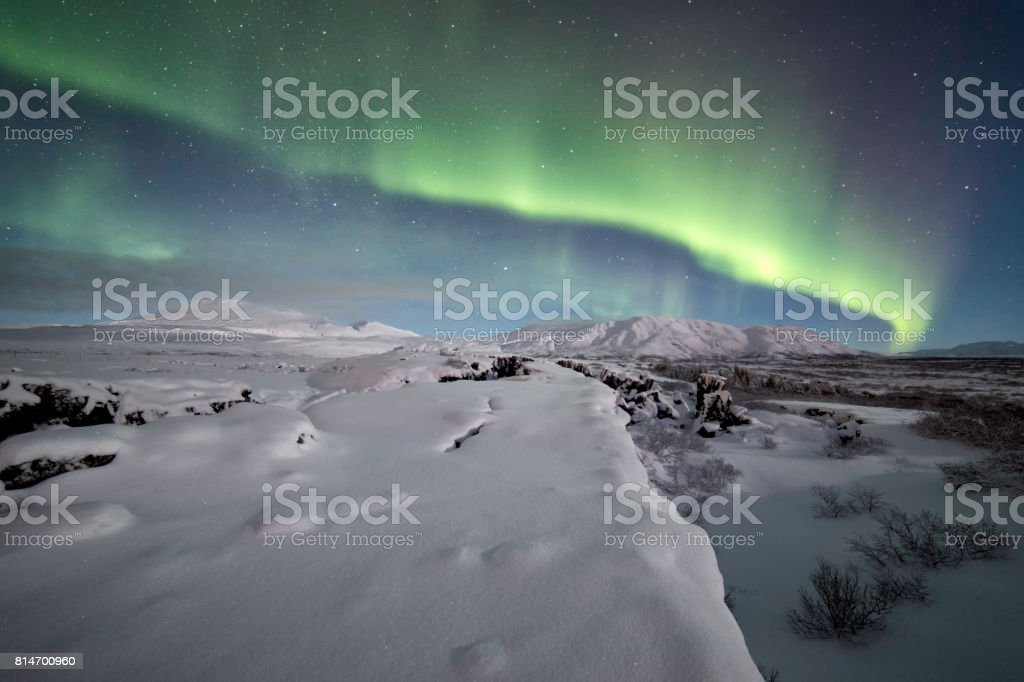 Northern lights over winter landscape stock photo