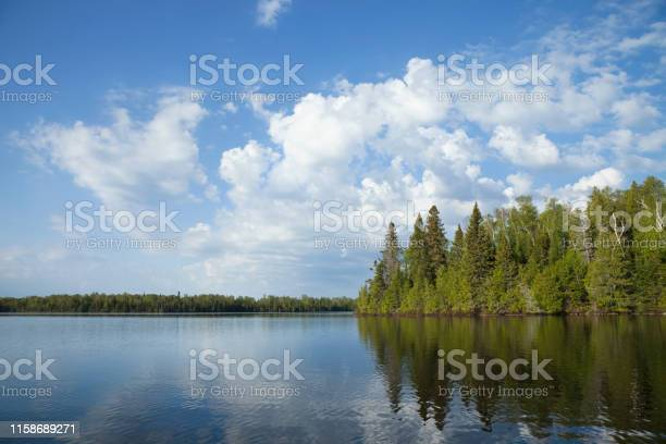 Photo of Northern Minnesota lake with trees along the shore and bright clouds on a calm morning