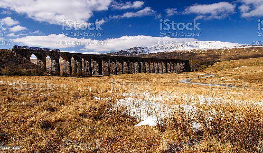 Northern Rail train on Ribblehead Viaduct Ribblehead, England, United Kingdom - April 1, 2013: A Northern Rail Class 158 diesel passenger train passes the snow-covered mountain of Whernside as it crosses Ribblehead Viaduct on the picturesque Settle-Carlisle Line Railway. Bridge - Built Structure Stock Photo