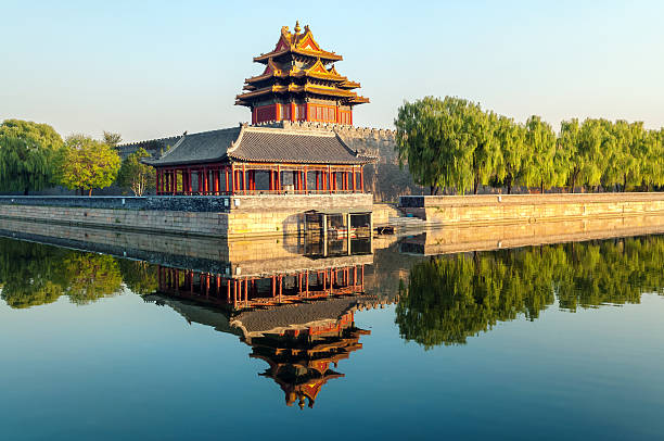 Northwest Wall of Forbidden City, Beijing China North west corner of the Forbidden City reflecting on water. Trees surrounding the corner, and clear sky.; Beijing, China forbidden city stock pictures, royalty-free photos & images