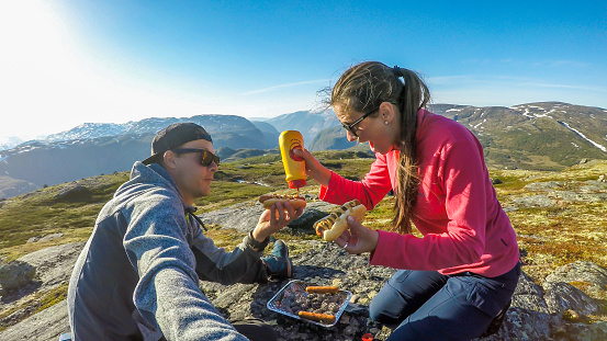 A couple having a grill in the tall mountains. Few sausages are being grilled. Couple uses portable one time grill, picnic grill. Girl spreads the mustard over the hot dogs. Camping in wilderness.