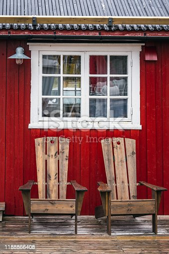 Window and chairs infront of traditional red wooden houses, rorbuer in the small fishing village of Nusfjord, Lofoten islands, Norway.
