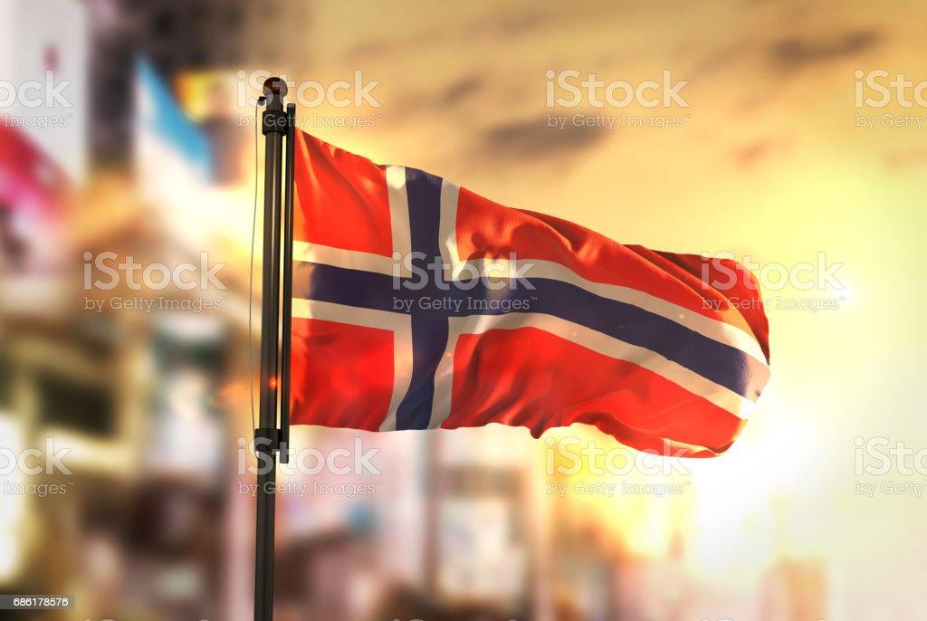 Norway Flag Against City Blurred Background At Sunrise Backlight - fotografia de stock
