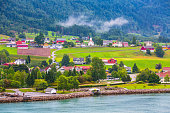 Norwegian village landscape with turquoise fjord water, mountains, church and colorful houses. Loen, Norway