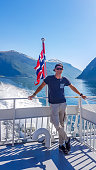 A young man leaning on a rail of a ship with a Norwegian flag waving behind him, Songefjorden, Norway. The motor of the ship makes the water wavy and foamy. Lush green mountains surrounding the fjord.
