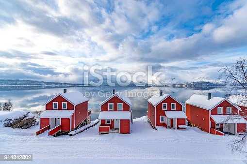 Norwegian cabin on the shore of a Fjord in Northern Norway in winter. Clouds over the Malangen fjord are bringing in new snow. The mountains in the background are reflected in the calm waters of the fjord.