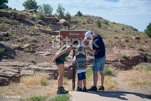 South Rim Canyon de Chelly National Park, July 7, 2019: Family of four tourist looking at an information sign at the Canyon de Chelly Tunnel Overlook along the canyon's south rim. There are two elementary school age children, twins at that, with their parent.