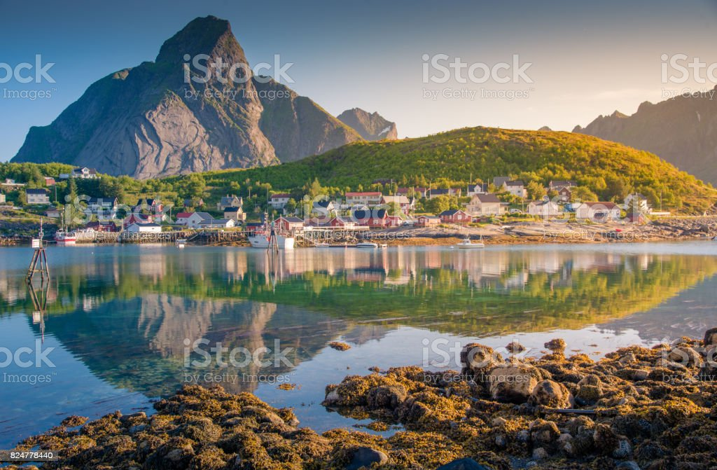 Norwegian fishing village  at the Lofoten Islands in Norway. Dramatic sunset clouds moving over steep mountain peaks. stock photo