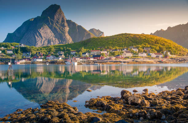 Norwegian fishing village  at the Lofoten Islands in Norway. Dramatic sunset clouds moving over steep mountain peaks. Norwegian fishing village  at the Lofoten Islands in Norway. Dramatic sunset clouds moving over steep mountain peaks. 4k resolution stock pictures, royalty-free photos & images
