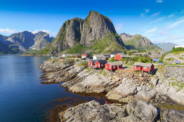 Aldeia de pescadores noruegueses nas ilhas Lofoten, na Noruega. Dramática do sol nuvens se movendo sobre picos de montanha íngreme. - foto de acervo
