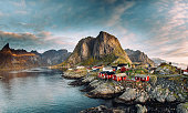 Norwegian fishing village at the Lofoten Islands in Norway. Dramatic sunset clouds moving over steep mountain peaks