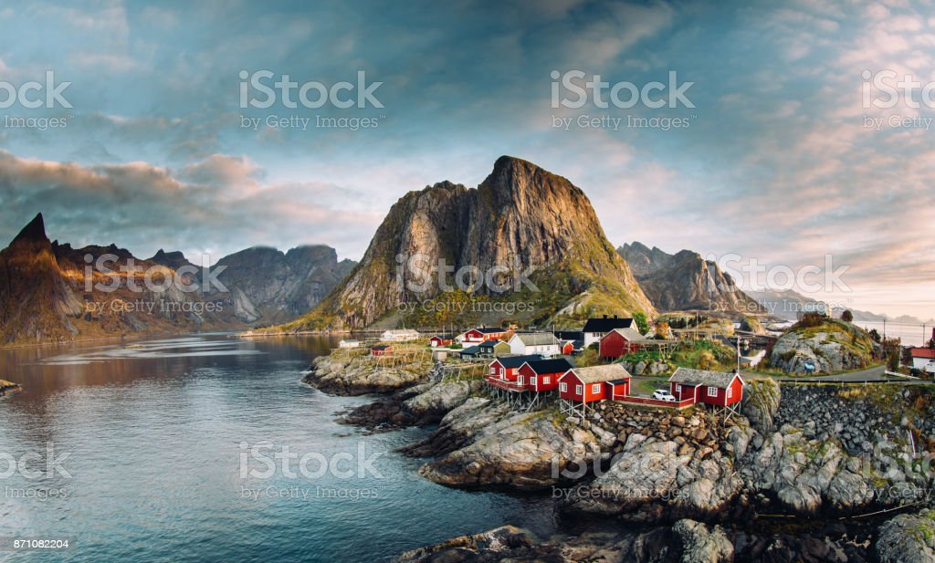 Norwegian fishing village at the Lofoten Islands in Norway. Dramatic sunset clouds moving over steep mountain peaks stock photo