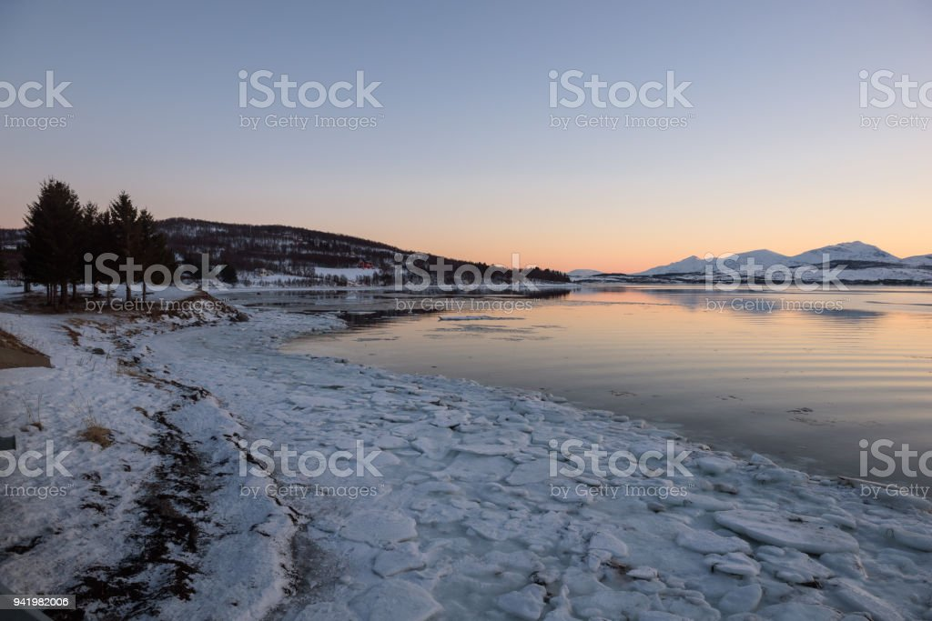 A Norwegian fjord near Tromsø covered with ice at sunset stock photo