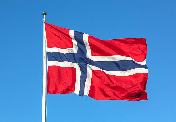 norwegian flag in red white and blue agianst the sky. - noorse vlag stockfoto's en -beelden