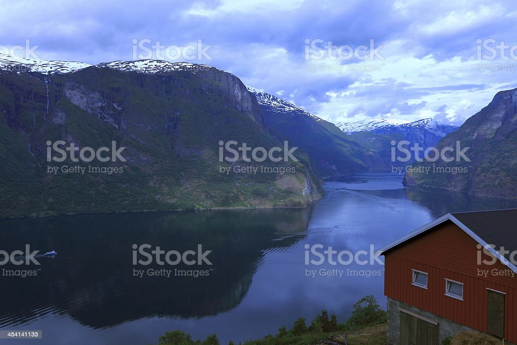 Norwegian house above Aurland fjord reflection and boat, Norway stock photo