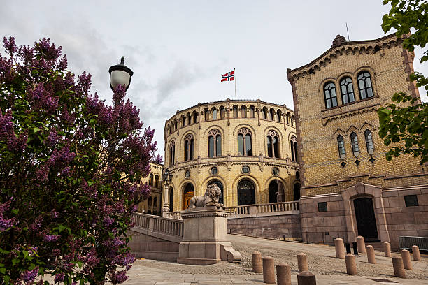 Norwegian parliament bulding with flag on roof in early May. Lilac trees in front of  the Norwegian Parliament Building with flag on the roof.    norwegian culture stock pictures, royalty-free photos & images