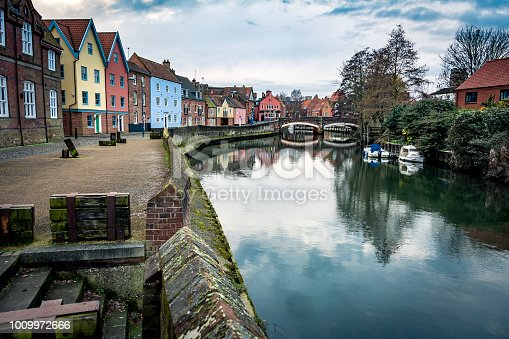 Building and bridge alongside riverside walk on the river Wensum in central Norwich