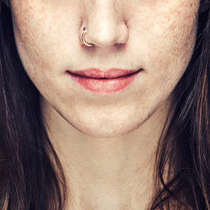 A beautiful close up portrait of an unrecognizable young woman's face from the nose to lower neck.  Natural makeup and a nose ring.  She has brown hair and freckles.  Square crop.