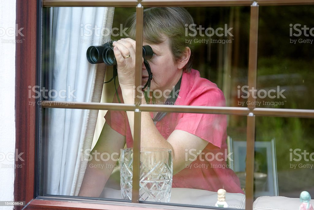 Nosey neighbour at the window with binoculars royalty-free stock photo