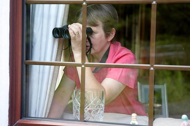nosey vicino alla finestra con binocolo - vicino foto e immagini stock