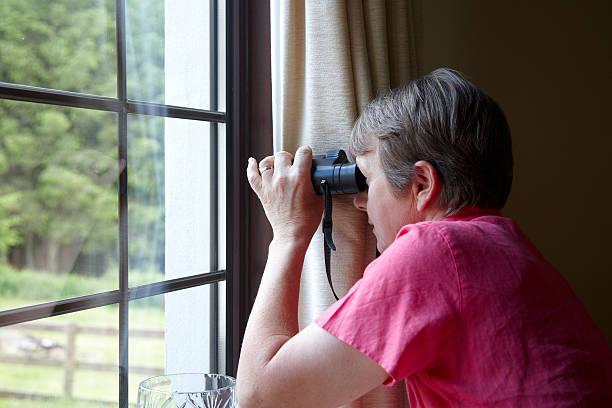 curieux voisin de la fenêtre avec des jumelles - indiscret photos et images de collection