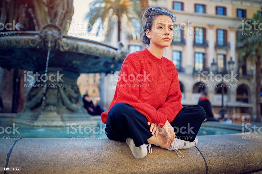 Nostagic girl is sitting on the fountain stock photo