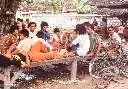 Nostalgia. Bali Indonesia, Kuta Beach 1976. Young men and boys resting on a bench by the beach. A bicycle is leaking against the bench.