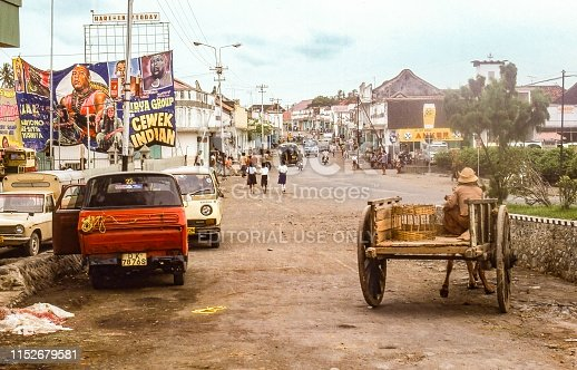 Nostalgia. Bali Indonesia, Singaraja 1978 Traffic on main street, cars, horse carriage bicycles and pedestrian. In the middle of the image three school children in uniform. Big advertisements for a movie. Dirt road.