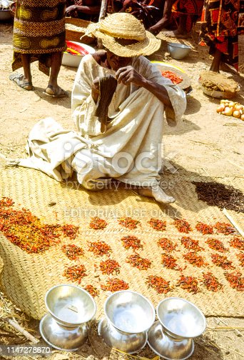 Nostalgia. Cameroon 1965. Traditionally dressed woman selling chilis at a rural market. She is sitting on the ground on a woven straw mat with small jeans of chilies and some metal bowls in front of her. People moving in the background.