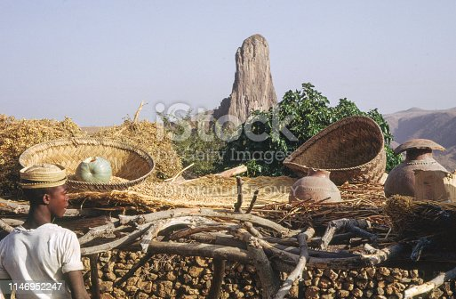 Nostalgia. Cameroon 1965. Young man looking at storing baskets in a village in Cameroon. Mountainformation in the background. +++ scanned slides from 1965 +++