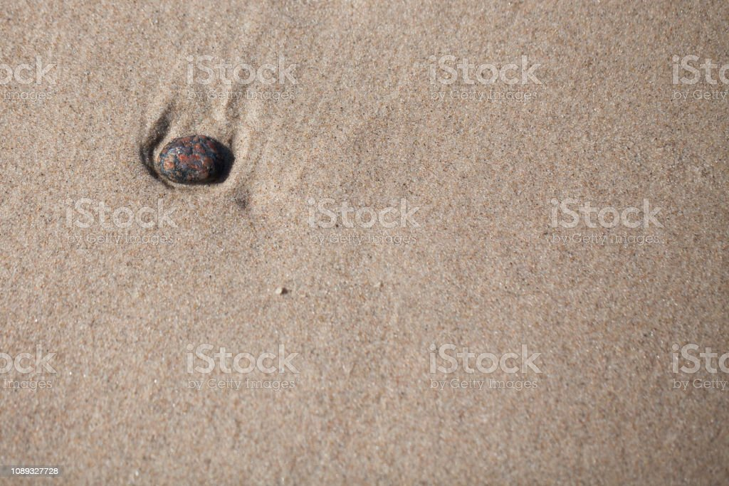 nostalgia - passing away, a stone lying on the beach washed by the sea. stock photo