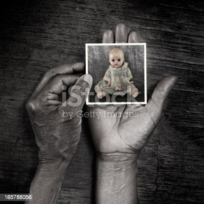 A photo of an old baby doll in the hands of a senior adult.