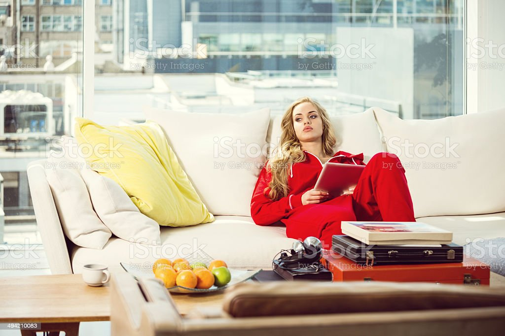 Nostalgia Pensive young woman relaxing on sofa at home, holding digital tablet in hands and looking away. 20-24 Years Stock Photo