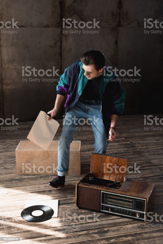 nostalgic man in vintage windcheater with vinyl record player royalty-free stock photo