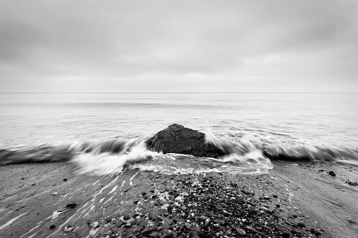 Nostalgic sea. Waves hitting in rock in the center. Black and white