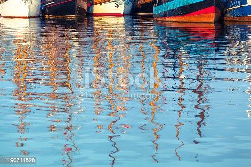 Row of vintage ship hulls at harbor, reflecting masts at blurred water surface foreground (copy space)
