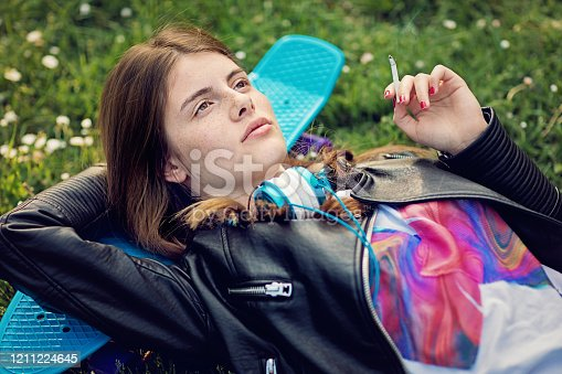 Nostalgic young girl is lying down and smoking cigarette