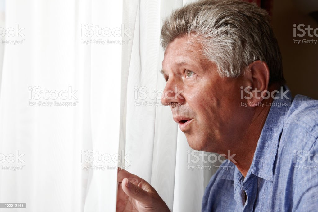 Nosy mature man at the window stock photo