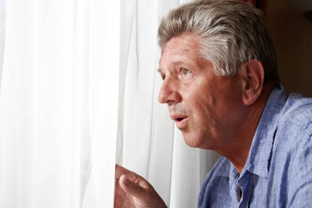 curieux homme mûr dans la fenêtre - indiscret photos et images de collection