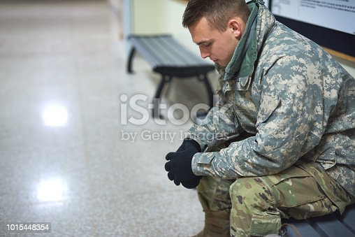 Shot of a young soldier sitting on a bench in the hall of a military academy