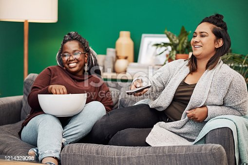 Shot of two young women having popcorn and watching tv together at home
