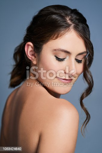 Studio shot of a beautiful young woman posing against a blue background