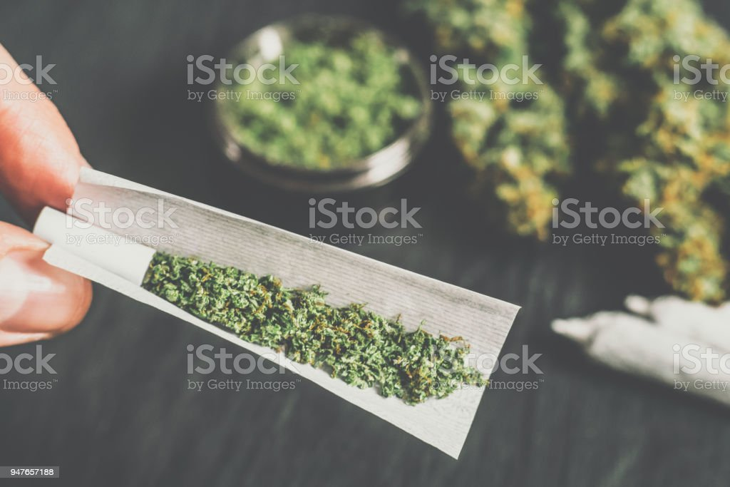 Not fully rolled jamb joint in the hands of a man marijuana weed Matting vintage color stock photo