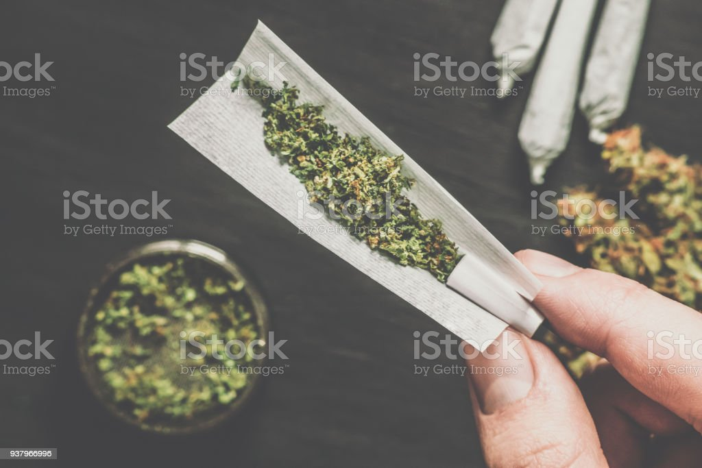 Not fully twisted jamb joint in the hands of a man marijuana weed Matting vintage color stock photo