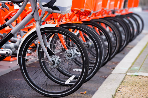 Not like all the other gray bicycle among orange ranked on a special parking lot for public use by fans of a healthy lifestyle and environmental and efficiency for the transport of health. stock photo