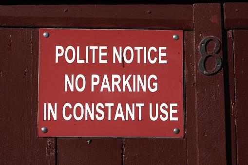 Printed sign on garage polite notice no parking